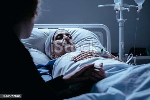 928968772 istock photo Dying senior woman with cancer in hospital bed with family support 1002255004