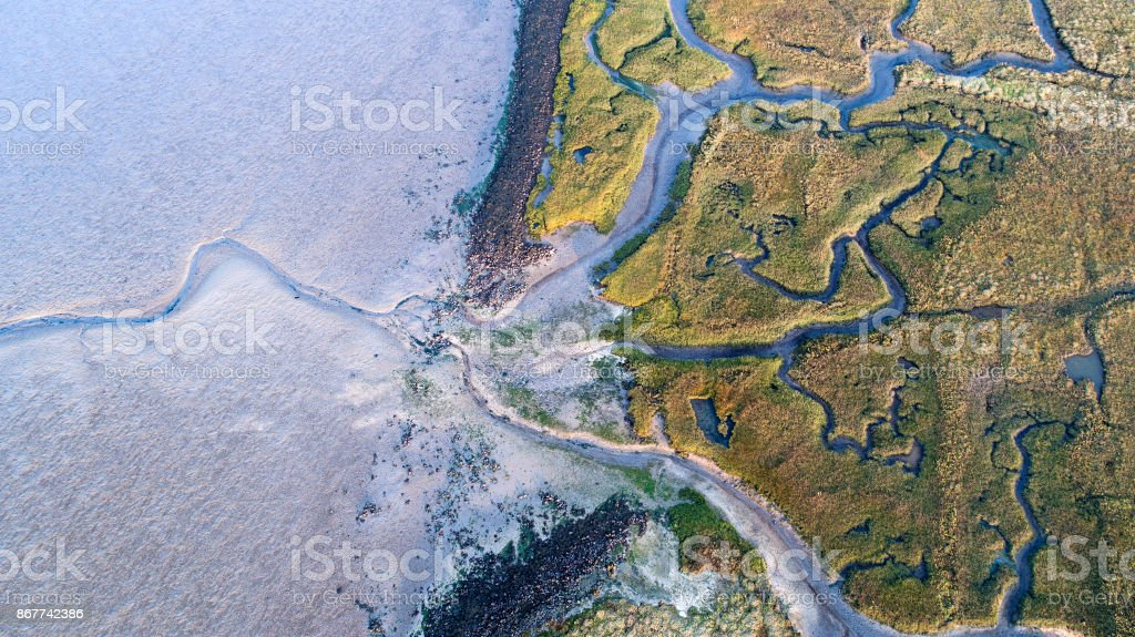 Dyke, salt marsh and coastline - aerial view stock photo