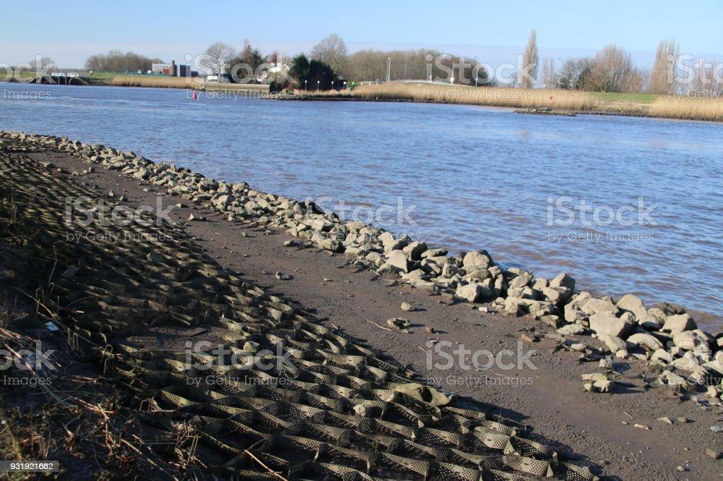 Dijk worden gerepareerd met losse stenen en asfalt langs rivier de Hollandse Ijssel in Gouderak dicht bij Gouda foto