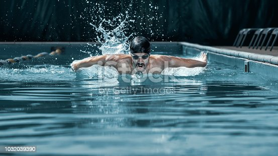 istock dynamic and fit swimmer in cap breathing performing the butterfly stroke 1032039390