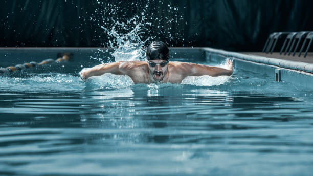 dynamic and fit swimmer in cap breathing performing the butterfly stroke - swimming stock pictures, royalty-free photos & images