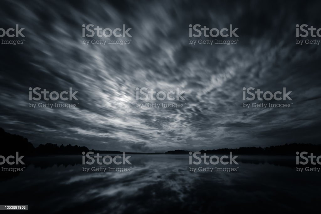 Dynamic clouds in the night over the lake lit by full moon, long exposure shot stock photo