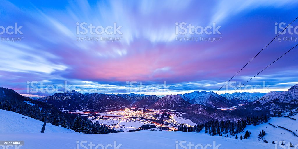 dynamic clouds over valley at winter night in tirol mountains stock photo