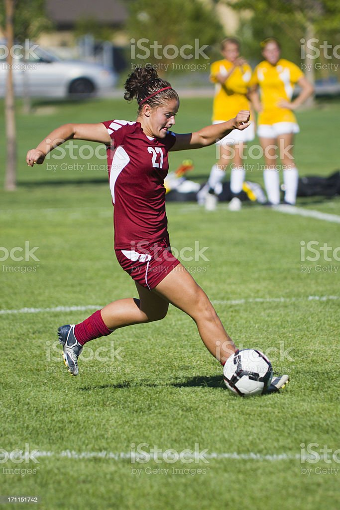 Dynamic Female Soccer Player Pounces in front of Rolling Ball royalty-free stock photo