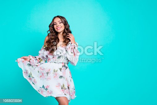 Dynamic image. Portrait of adorable, good-looking, magnificent person hold the hem of the dress look at camera with white hollywood smile touch brunette hair isolated on vivid turquoise background