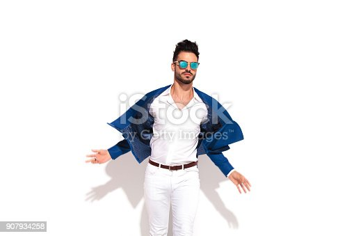 907934274 istock photo dynamic picture of an elegant man in sunglasses opening coat 907934258