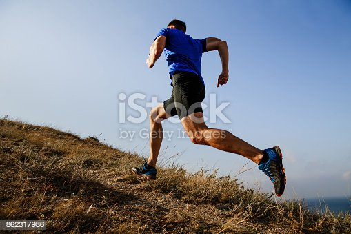 istock dynamic running uphill on trail male athlete runner side view 862317986