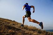 ダイナミックなトレイル男性アスリート ランナー サイドビューの上り坂を実行します。