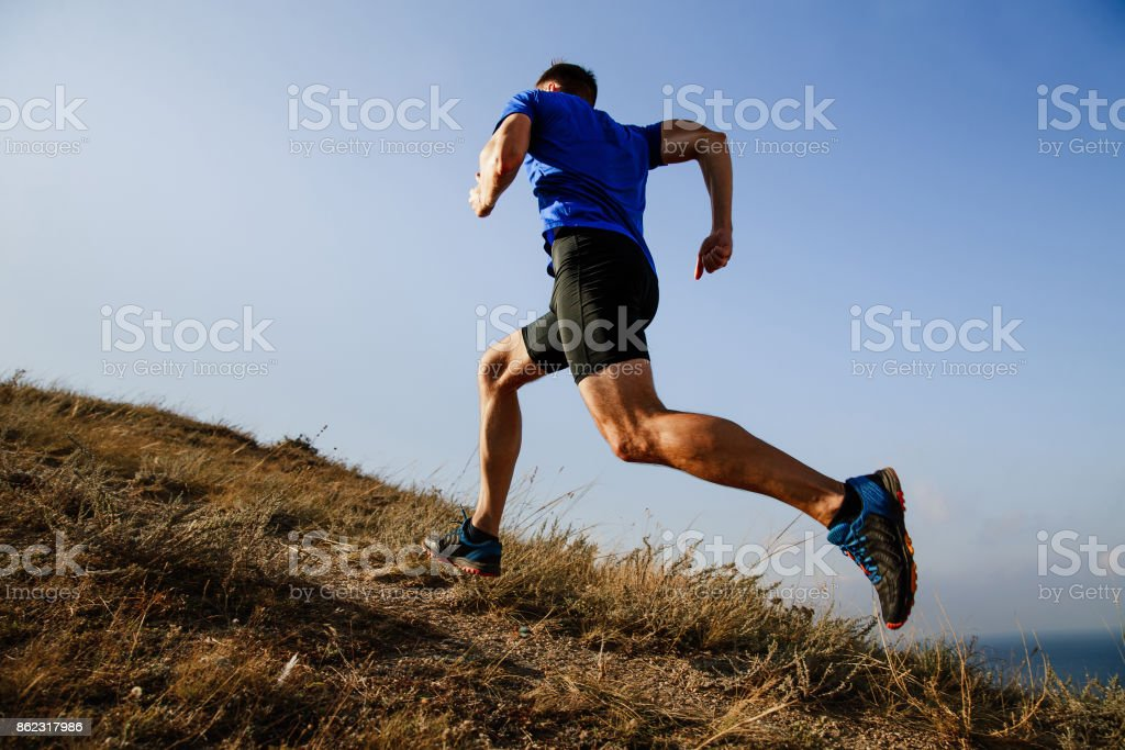 dynamic running uphill on trail male athlete runner side view stock photo