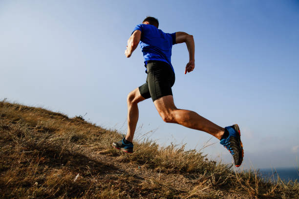 dynamic running uphill on trail male athlete runner side view - jogging stock pictures, royalty-free photos & images