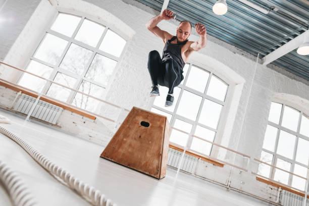 Dynamischer Schuss von fitter Athleten springen über Cross-Kasten im Fitness-Club. Starker Mann macht Sprungübungen im Fitnessstudio – Foto