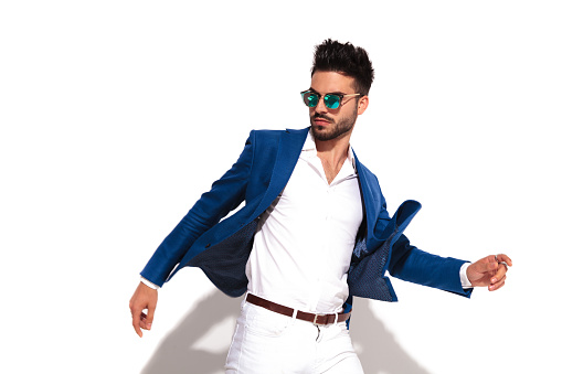 dynamic side picture of a smart casual man in sunglasses walking on white background