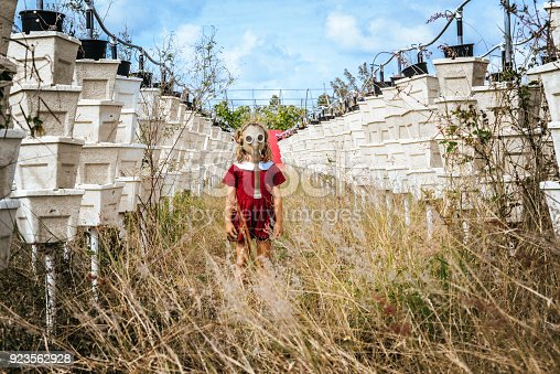 Young child in a vintage looking photograph stands in an empty field of overgrown weeds and empty vertical gardens wearing a gas mask. Commentary on pollution, pesticides, and a dystopian future