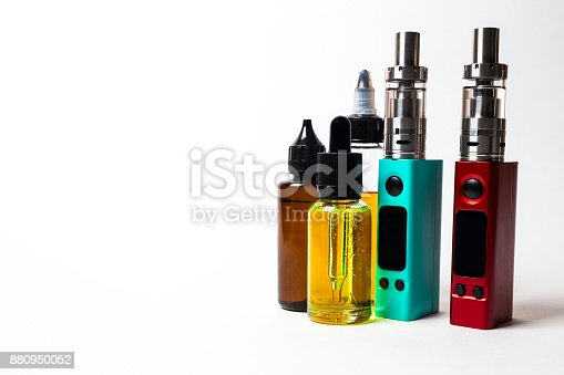 880947556 istock photo e- liquid, e-juice in the bottles and e-cigarette (vape)  isolated on the white background with copyspace 880950052