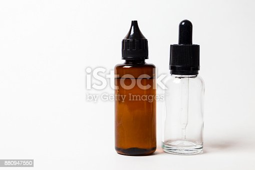 880947556 istock photo e- liquid, e-juice in the bottles isolated on the white background with copyspace 880947550