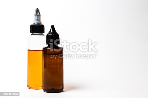 880947556 istock photo e- liquid, e-juice in the bottles isolated on the white background with copyspace 880947564