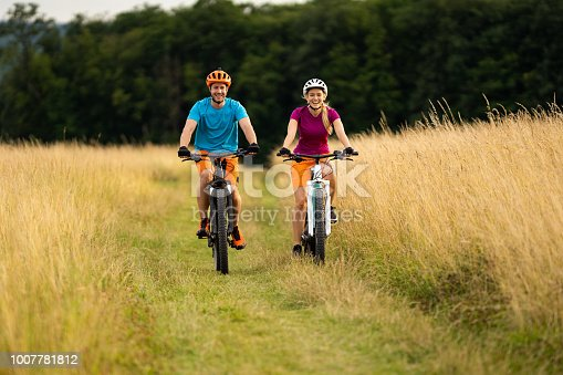 istock e mountain biking couple in grassland 1007781812