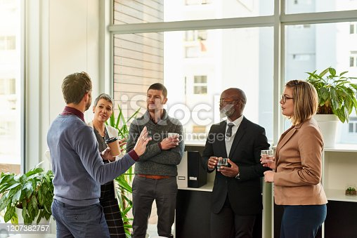 Shot of a group of businesspeople standing together while having a discussion in a modern office