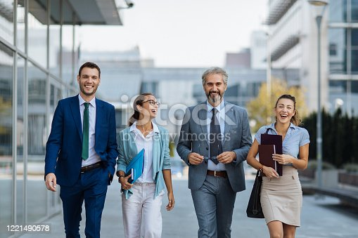 Four smiling colleagues walking next to an office building on their way to a meeting