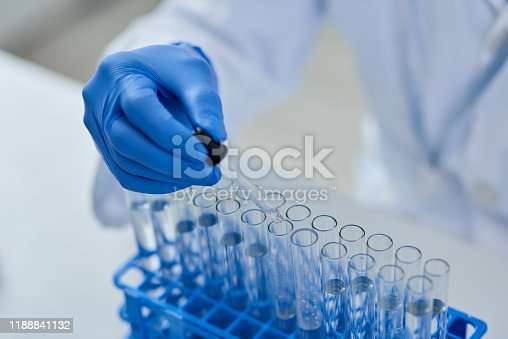 Closeup of an unrecognizable scientist pouring a substance into test tubes to do experiments on inside of a laboratory during the day