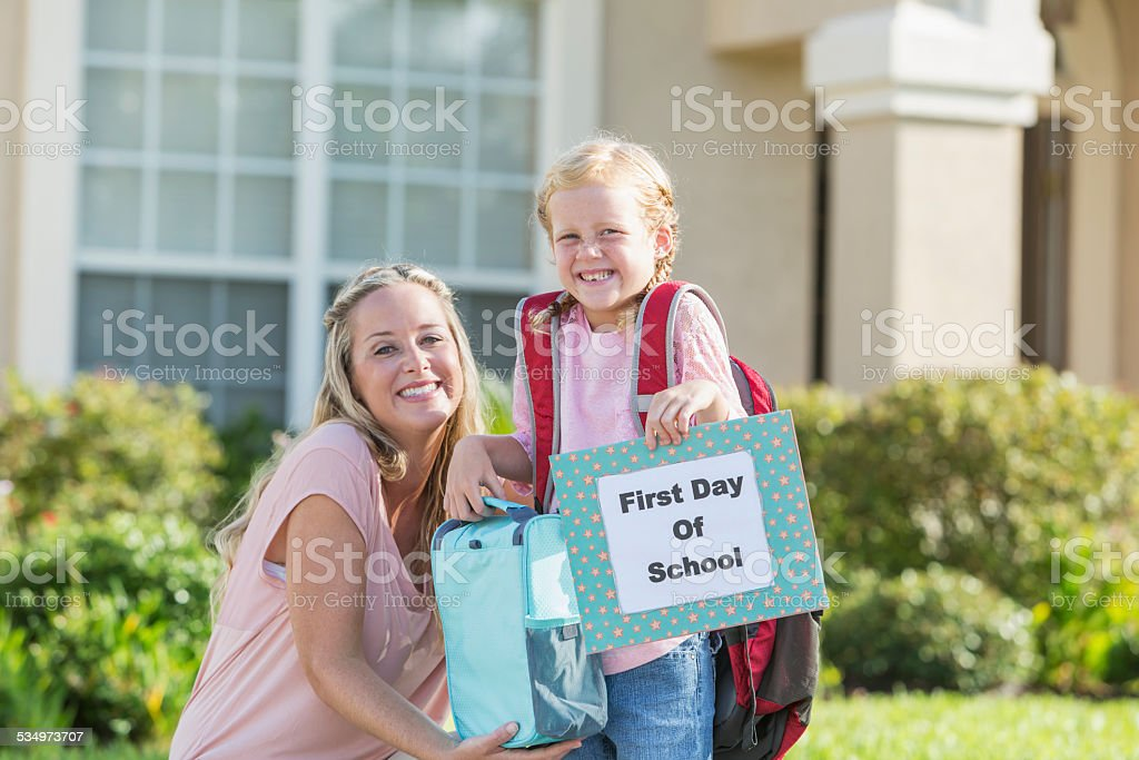 Eager child with mother ready for first day of school stock photo