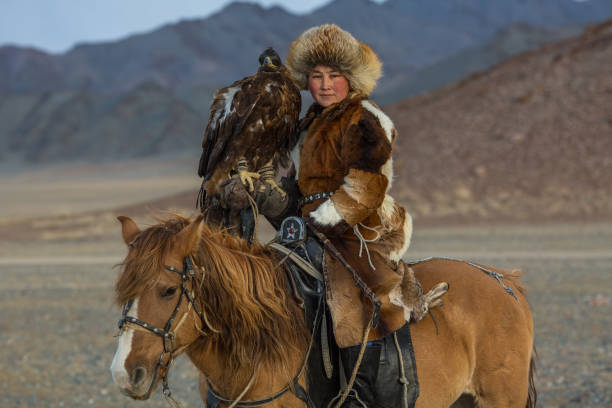 Eagle Hunter in desert mountain of Western Mongolia. Kazakh woman Eagle Hunter traditional clothing, while hunting to the hare holding a golden eagle on his arm in desert mountain of Western Mongolia. independent mongolia stock pictures, royalty-free photos & images