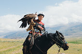 istock Eagle Hunter in traditional costume riding horse with Golden Eagle in the mountains of Central Asia 1343808555