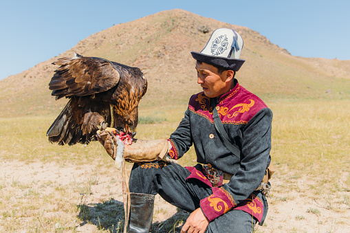 Portrait of a man hunter and his Eagle eating its prey -  an old tradition of eagle hunting in the wilderness area of Tian Shan mountains, Kyrgyzstan