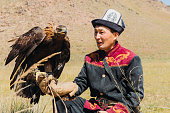 istock Eagle Hunter in traditional costume with Eagle in the mountains of Central Asia 1343808646