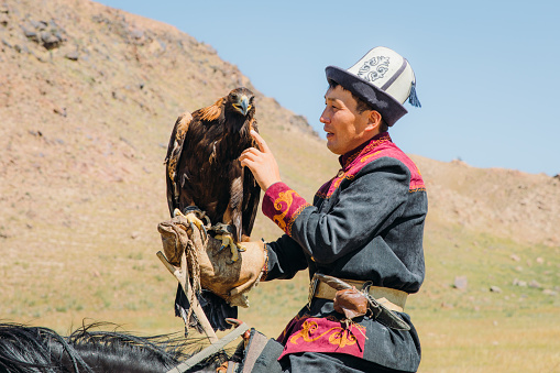 Portrait of a man hunter and his Eagle doing an old tradition of eagle hunting in the wilderness area of Tian Shan mountains, Kyrgyzstan