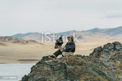 Eagle hunter on the background of lake in Gobi desert in Mongolia