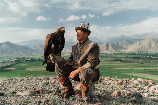 Eagle hunter sitting on the background of mountains  in Kyrgyzstan