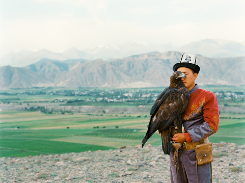Eagle hunter standing on the background of mountains  in Kyrgyzstan