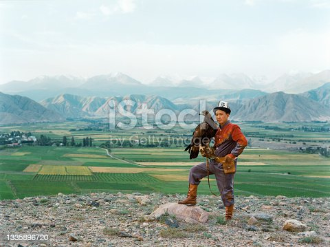istock Eagle hunter standing on the background of mountains  in Kyrgyzstan 1335896720