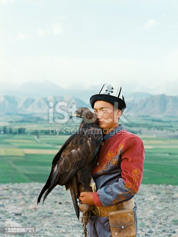 istock Eagle hunter standing on the background of mountains  in Kyrgyzstan 1335896721