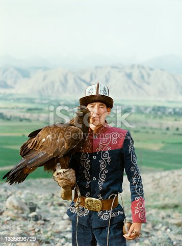 istock Eagle hunter standing on the background of mountains  in Kyrgyzstan 1335896729