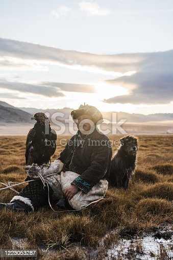 Eagle hunter with dog  in steppe in Mongolia