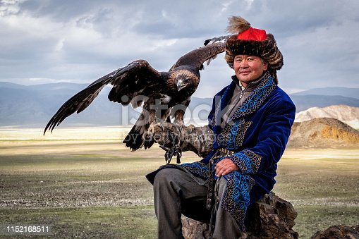 Eagle Hunter with his golden eagle in Bayan-Olgii, West Mongolia. Hunting with eagles is a traditional form of falconry found throughout the Eurasian Steppe.