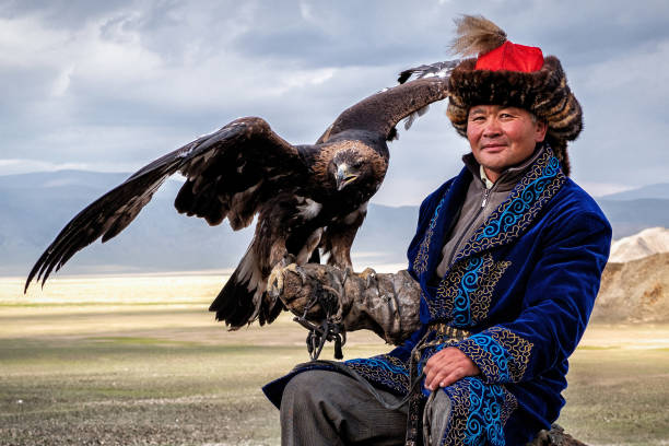 Eagle Hunter with His Eagle in Bayan Olgiy, West Mongolia Eagle Hunter with his golden eagle in Bayan-Olgiy, West Mongolia. mongolian culture stock pictures, royalty-free photos & images