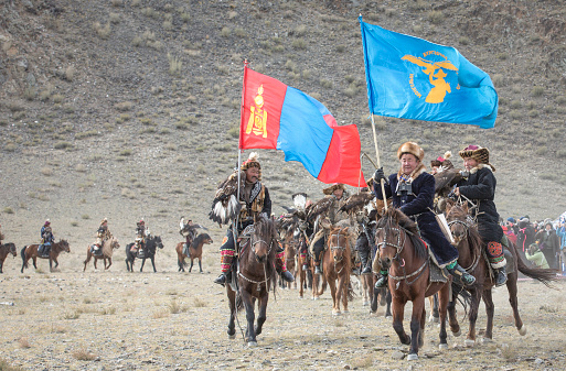 Bayan Ulgii, Mongolia, October 4th, 2015: Eagle hunter riding a horse  with his Altai Golden Eagle
