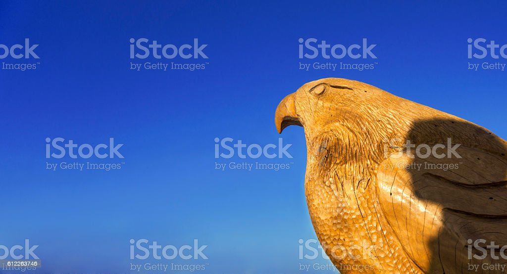Eagle wooden sculpture and the shadow of a person. stock photo