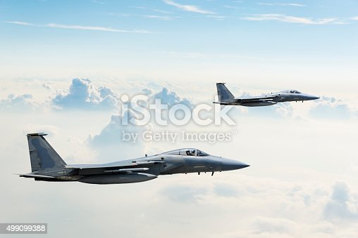 Two F-15 Eagle fighter jets flying above clouds