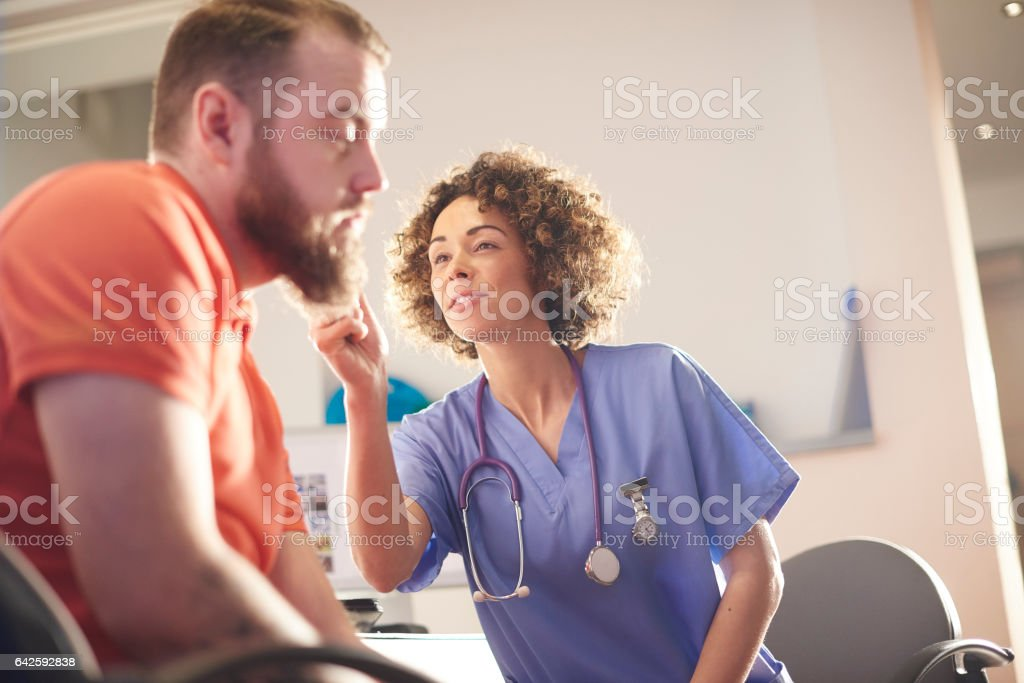 a female doctor sits and chats to a male patient who we see from...