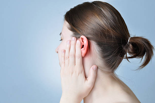 Ear inflammation Young woman touching her inflamed ear human ear stock pictures, royalty-free photos & images