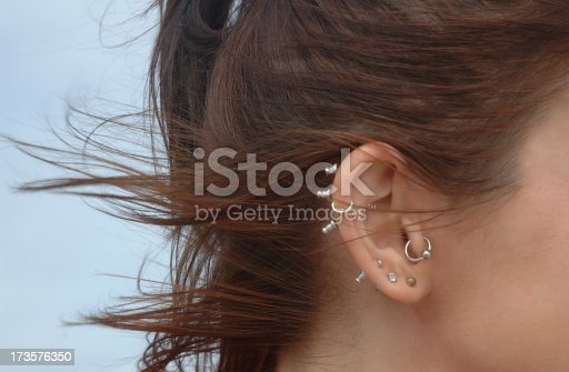 Close-up of multiple ear piercings on young woman with wind-swept hair. Slightly soft focus.