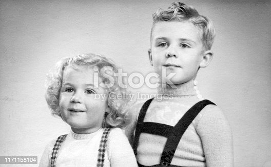 Early 1950s duo portrait of a young boy and girl with blond hair and curls.