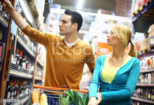 Early 30's caucasian couple buying food in local supermarket.The guy is reaching for the bottle of wine while she's leaning over the cart.They are at dairy products aisle. Wearing green and brown casual shirts.