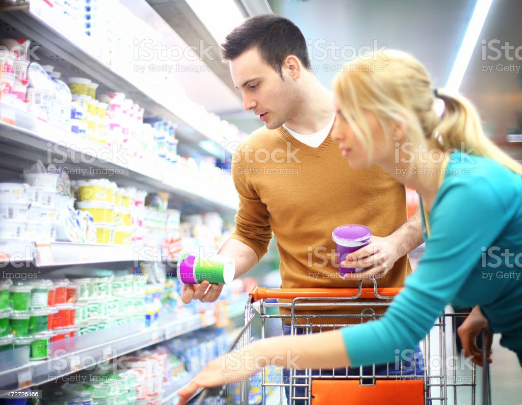 Early 30's man and woman shopping in supermarket. stock photo
