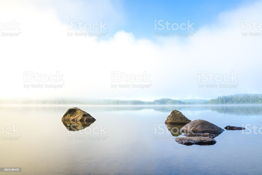 Early and harmonious morning with fog over the lake stock photo