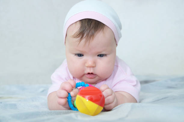 Early brain development. concentrated little baby girl  playing with rattle stock photo